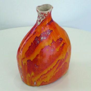Variagated orange glazed ceramic vessel titled Torso
